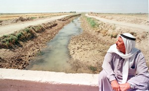 IRAQI FARMER SITS BESIDE A NEARLY DRY RIVER.