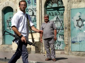 A Jewish settler walks past a Palestinian on Shuhada Street  in the West Bank city of Hebron. Nayef Hashlamoun Reuters