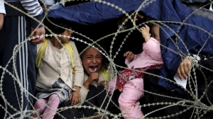 A little girl cries as she tries to take shelter from the rain on Greece's border with Macedonia Photo Reuters