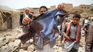 A man displays the bloodied shirt of a child victim at the rubble of houses destroyed by an Saudi air strike in the Okash village near Yemen's capital Source Telesurtv