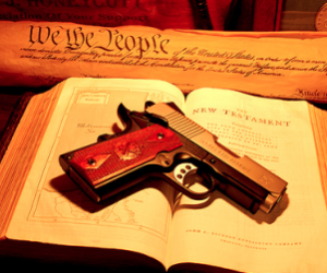 A gun on the Bible with the Constitution. Source San Diego Free Press