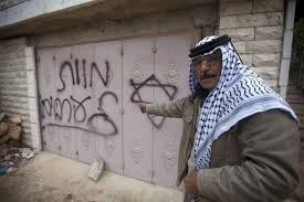 """A Palestinian man points to Hebrew graffiti reading """"Death to the Arabs"""" following an arson attack in Khirbet Abu Falah, northeast of the West Bank city of Ramallah, Sunday, Nov. 23, 2014. Source Ma'an News."""