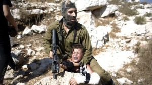 An Israeli soldier puts a Palestinian boy in choke hold for allegedly throwing rocks at Israeli tanks. Source Ha'aretz.