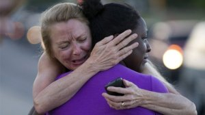 Survivors comfort each other following the Aurora mass shooting. Photo Getty Images.