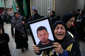 A relative of Samer Huhu, who was killed in a twin bombing attack in Beirut, waves his portrait. Source Associated Press.