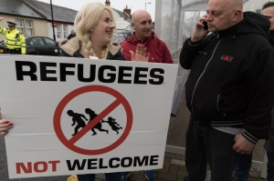 A woman holds an anti-refugee sign at a rally in Scotland. Photo source, Vice.