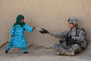 U.S. Army Private First Class Danny Comley of Camdenton Missouri, assigned to Delta Company 4th Brigade combat team,2-508, 82nd parachute infantry Regiment, receives flowers from an Afghan girl during a patrol in the Arghandab valley in Kandahar province, southern Afghanistan February 24, 2010. REUTERS/Baz Ratner (AFGHANISTAN - Tags: CIVIL UNREST CONFLICT IMAGES OF THE DAY) - RTR2ATJB