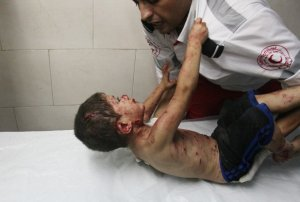 A boy in Gaza is calmed and treated at a besieged hospital in Gaza during Israel's assault.  Source Getty.