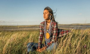 a-native-american-woman-sits-on-a-bluff-in-north-dakota-at-the-pipeline-protest-source-the-guardian