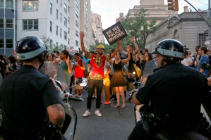 Protesters, marching against the killing of Alton Sterling and Philando Castile, hold placards towards members of the New York Police Department on motorbikes in Manhattan, New York, U.S., July 7, 2016. Picture taken July 7, 2016. REUTERS/Bria Webb - RTX2KE8I